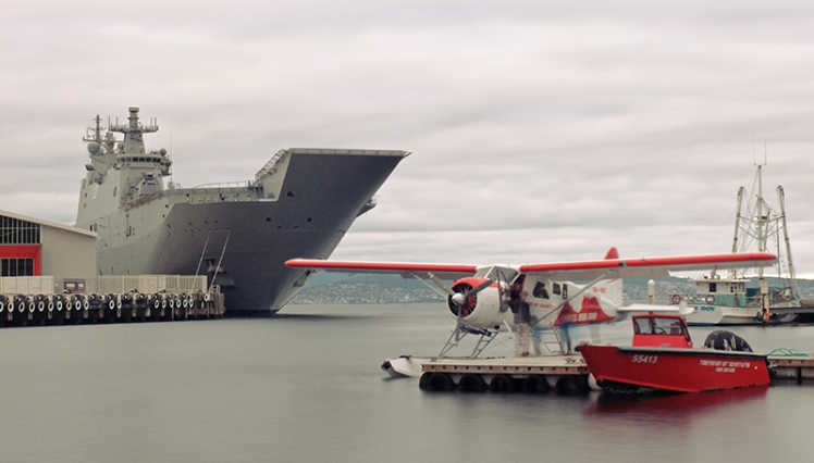 HMAS Canberra looms over the Tasmanian Air Adventures plane in Sullivan's Cove.