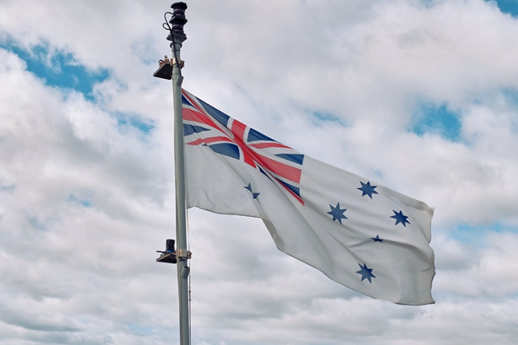 The Australian White Ensign flutters proudly in the breeze.
