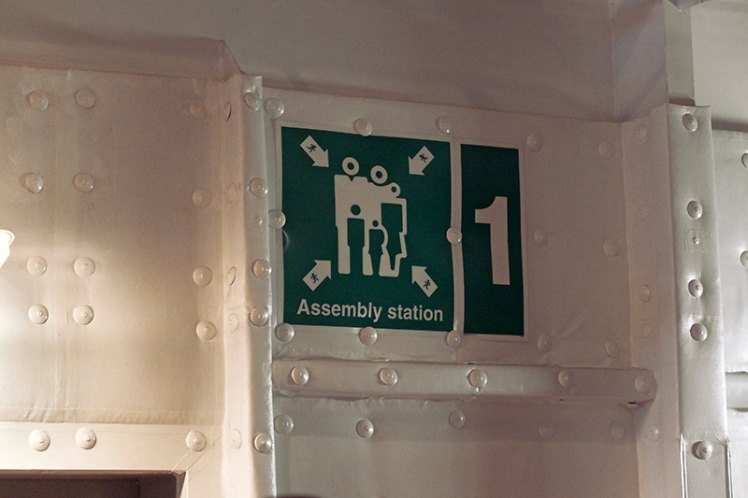 In case of emergency people should run towards the small green people trapped inside the larger group of white people from all four corners.