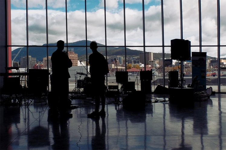 A young musician chats with one of the Navy band members in the cruise-ship terminal overlooking Hobart.