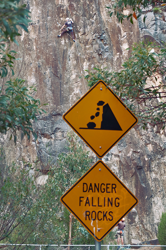 A climber pays no heed to the warning signs at the cliffs near the start of Waterworks Road.