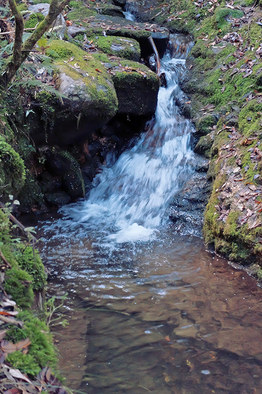 A tiny waterfall runs down a man-made run off channel .