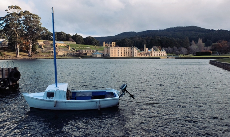 A small dinghy sits in the harbour overlooking the site.