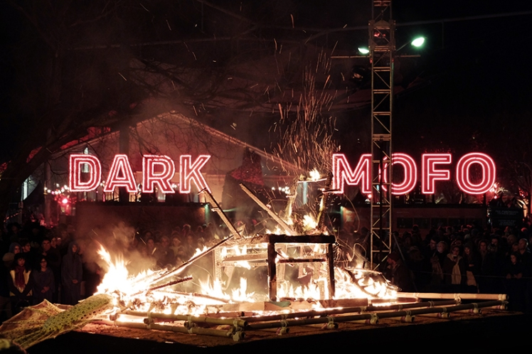 The last embers of the fish burn down in front of the Dark Mofo sign.