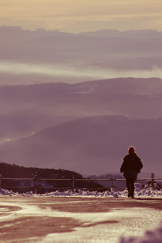 A lady ventures back down the mountain, layer after layer of hills before her.